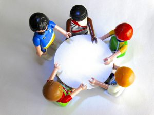 besluitvorming aan ronde tafel met playmobilpoppetjes